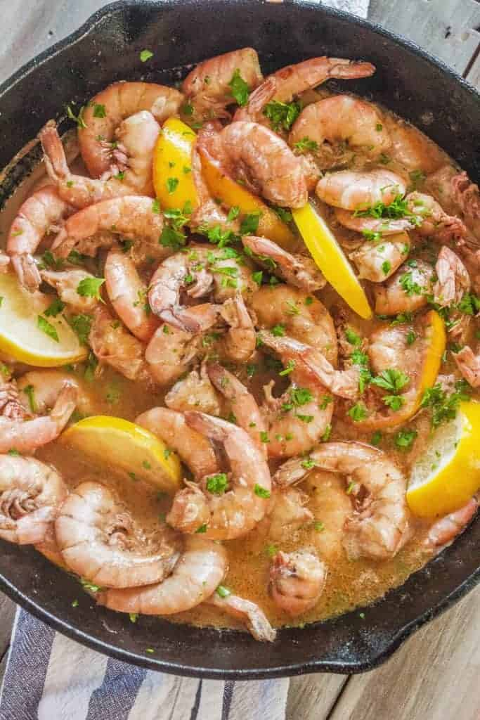 shrimp in a cast iron skillet cooked in a buttery savory broth.