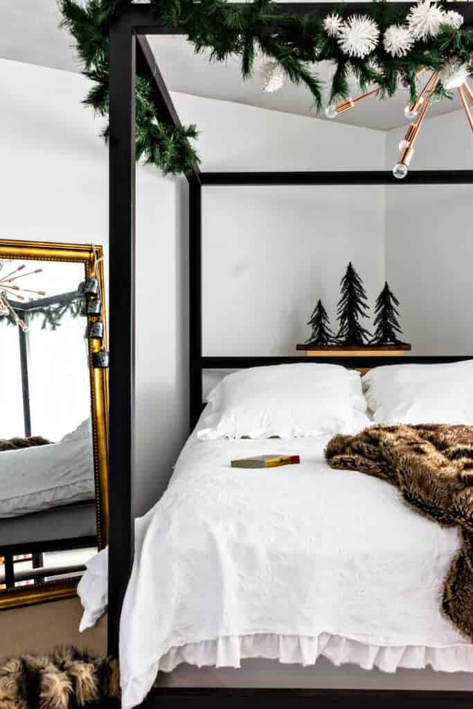 New traditional Christmas decorations in bedroom. Black metal four poster bed, white bedding with greenery and white pom pom garland.