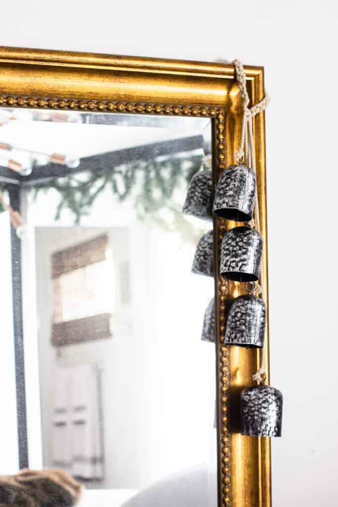 Full length gold mirror in bedroom, with silver Christmas bells. New traditional Christmas decorations in bedroom.