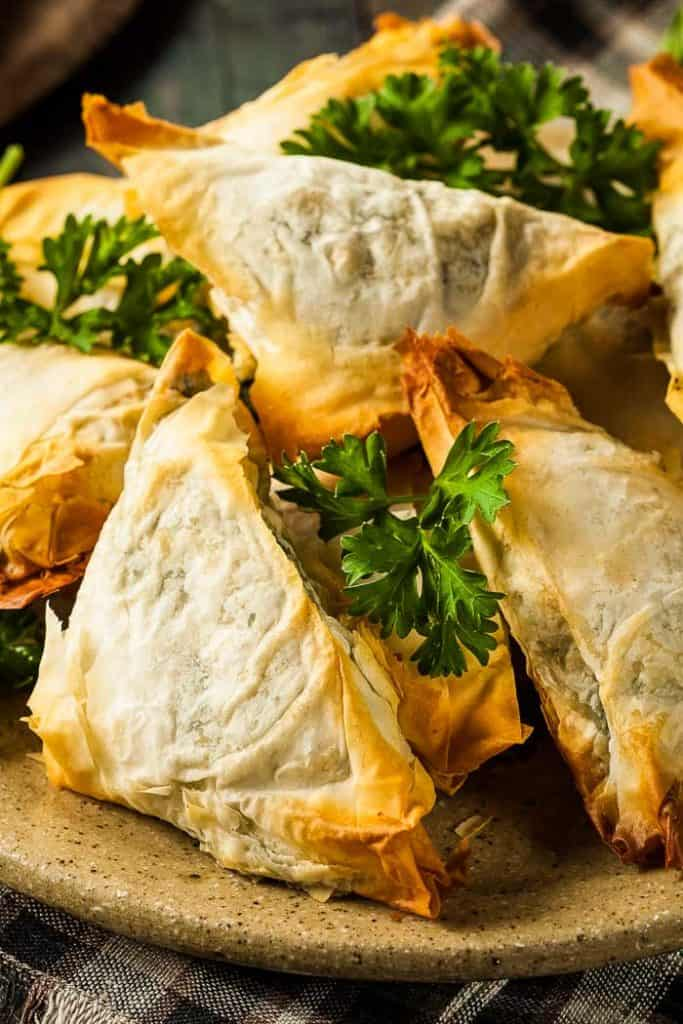 spanakopita or spanikopita on a plate with a bright green parsley garnish