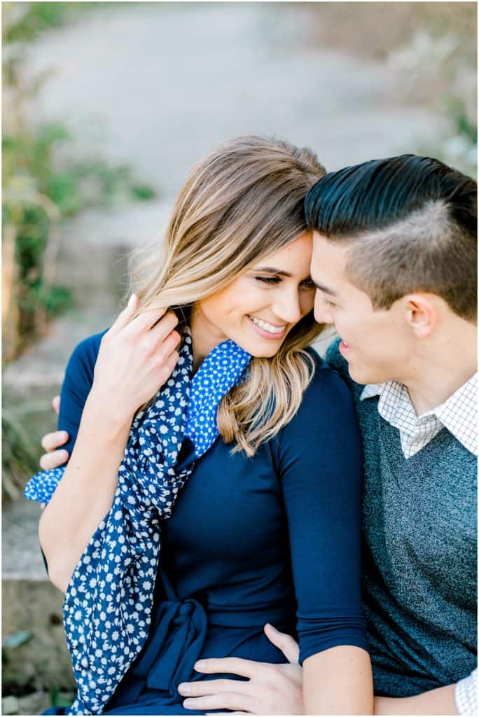 couple's engagement session , looking at each other and smiling she is holding her hair