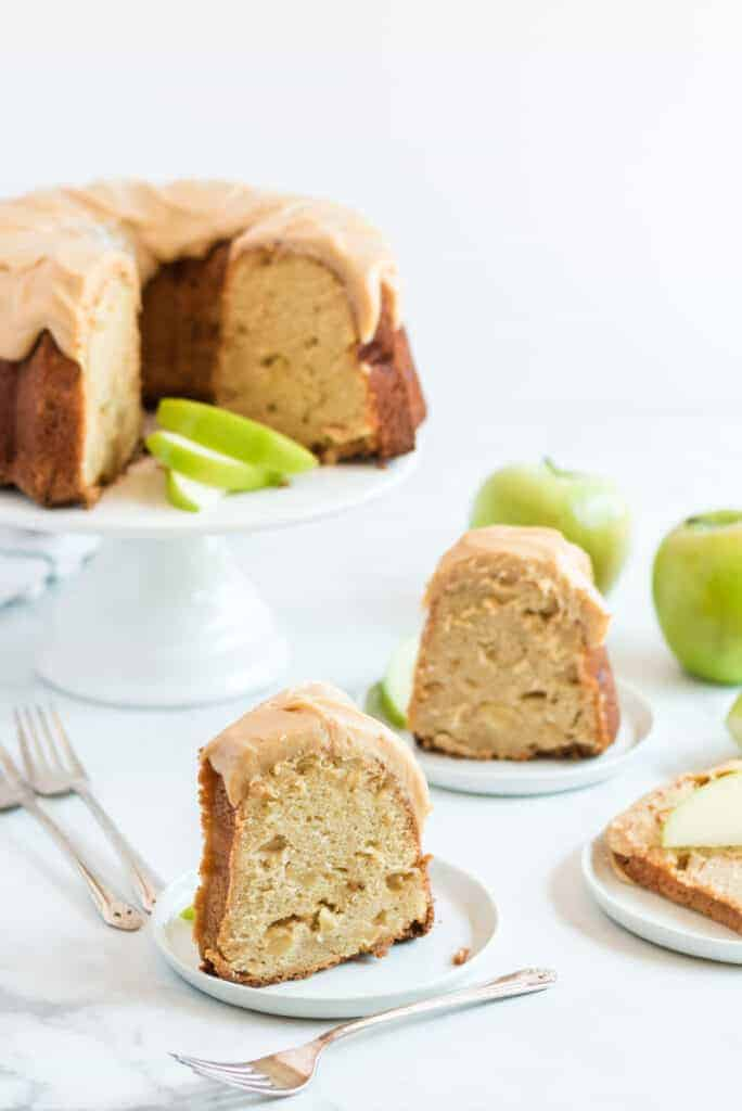 caramel apple pound cake with frosting ready to eat on a white pedestal