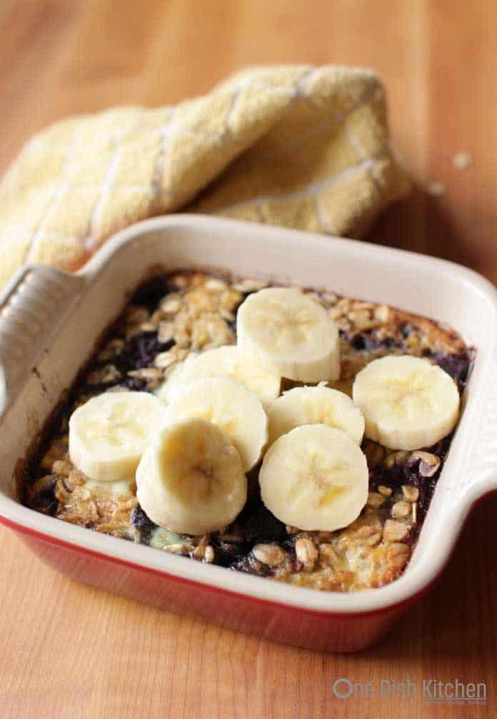 Baked Oatmeal with blueberries in a small baking dish topped with banana slices