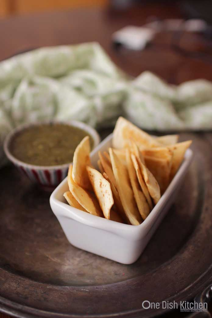 A small bowl of homemade tortilla chips next to a small bowl of green salsa all on a metal tray