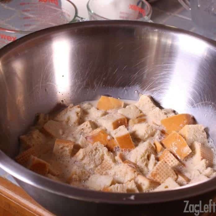 cubes of bread in a large bowl soaking in milk and eggs.