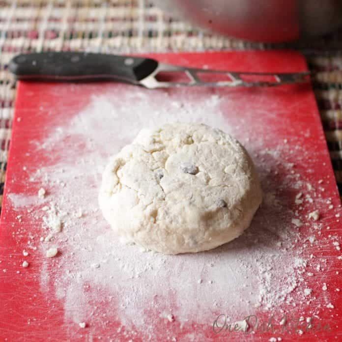 Irish soda bread dough sitting on a cutting board next to a knife