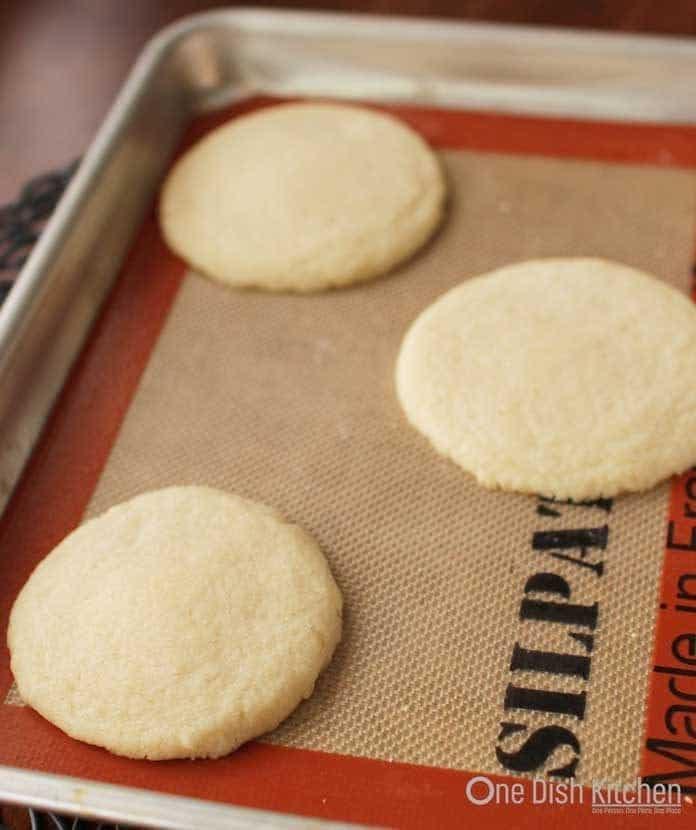 Three shortbread cookies on a baking sheet
