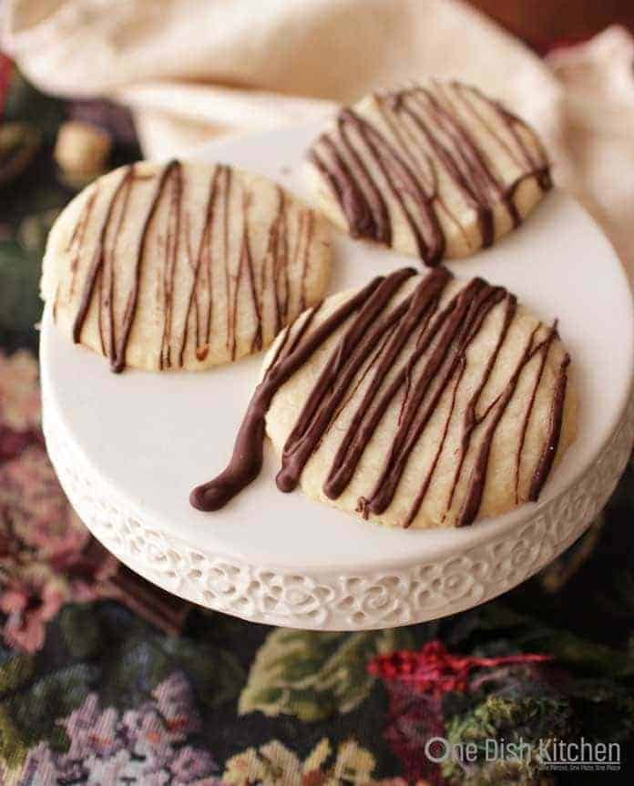A plate of three shortbread cookies drizzled with melted chocolate