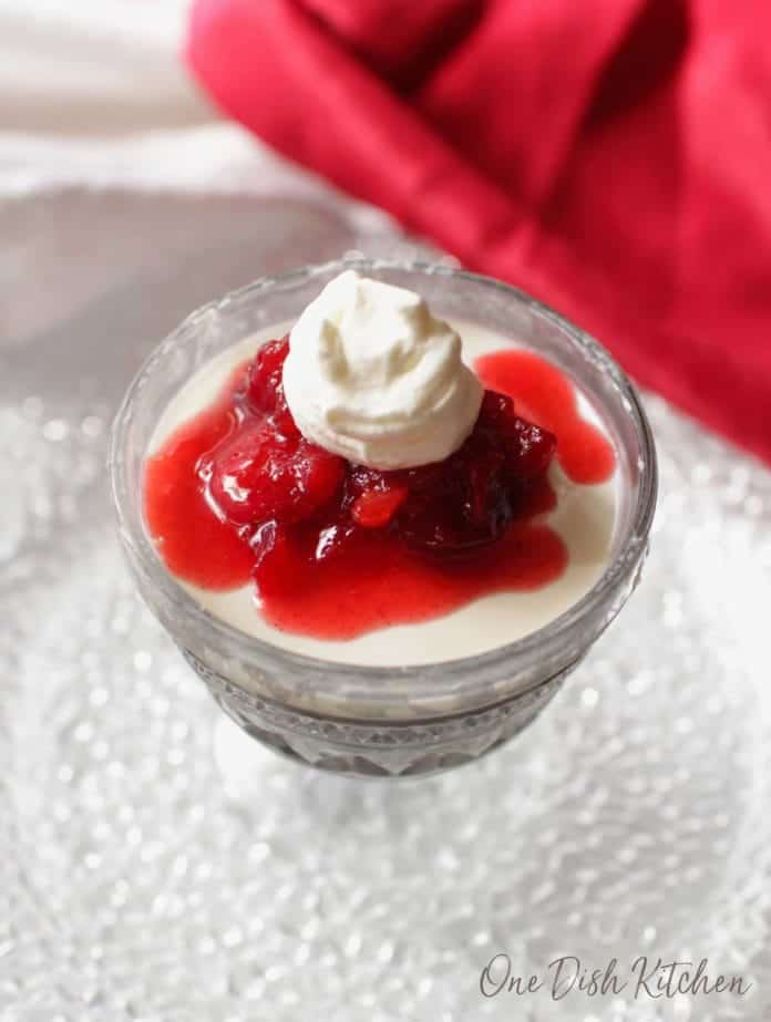 panna cotta in a small bowl with cranberry jam spooned over the top.