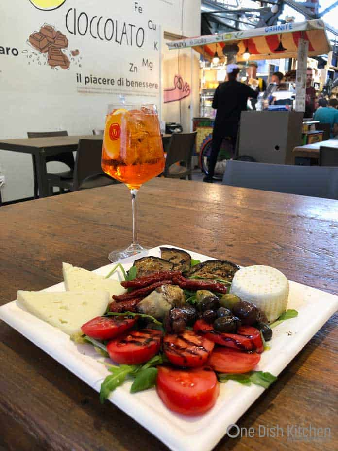 Enjoying and Aperol Spritz at an outdoor market with a plate of assorted appetizers