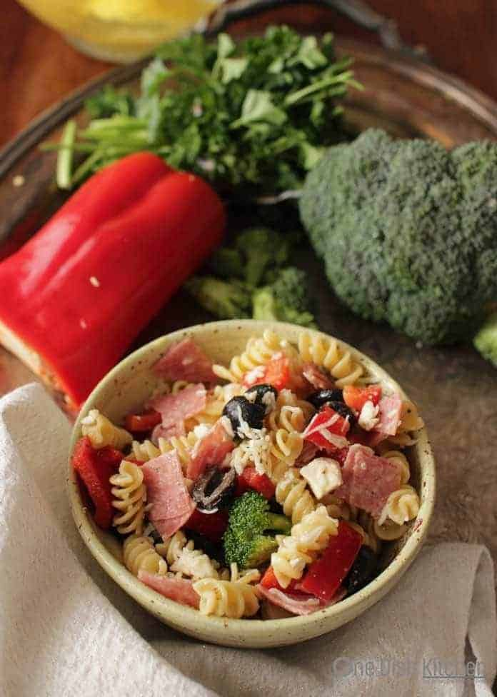 A bowl of Italian pasta salad with italian dressing on a metal tray with a red pepper and a head of broccoli