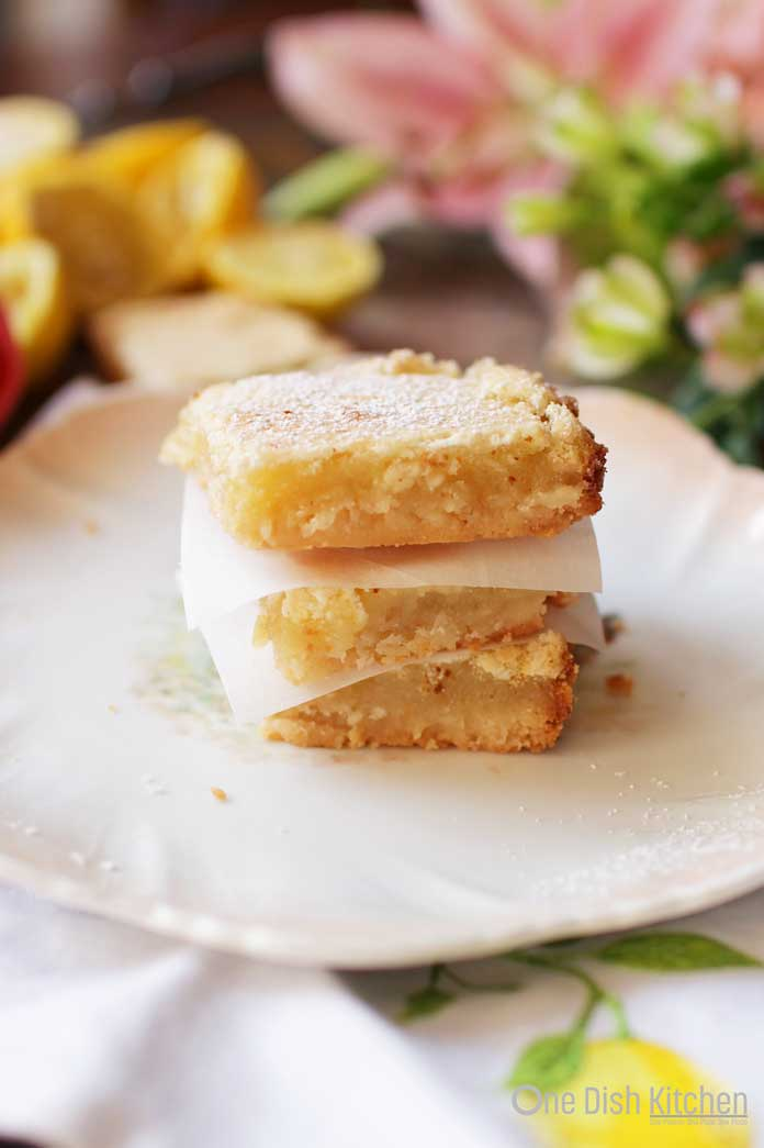 A stack of three lemon bars on a plate with lemon slices and pink flowers in the background