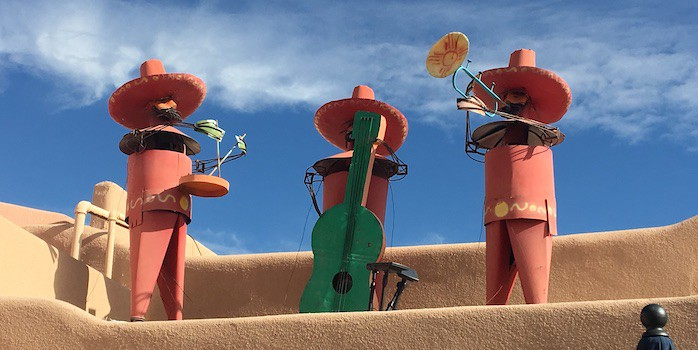 3 colorful mariachi statues on an adobe roof top in old town albuquerque.