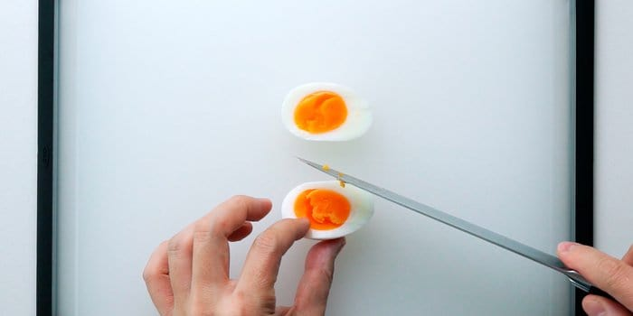 Cutting a medium boiled egg in half for a sandwich.