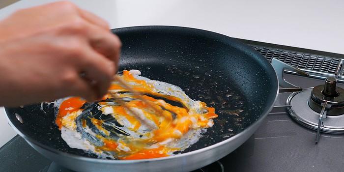 Scrambling egg in a frying pan.