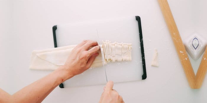Hand-cutting udon noodles with a knife.