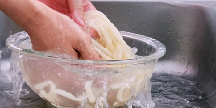 Washing boiled udon noodles in cold water.