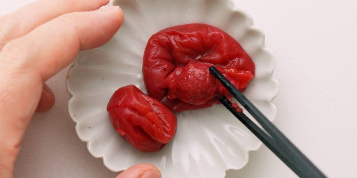 Removing pits from Umeboshi with chopsticks.