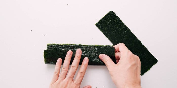 Cutting nori into strips for wrapping rice balls.