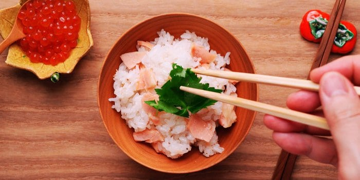 Garnishing a bowl of salmon rice with Matsuba.