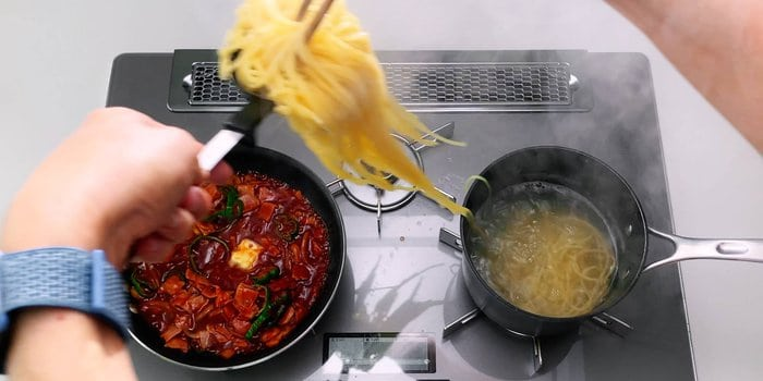 Transferring boiled spaghetti to a pan with the sauce for making Japanese Napolitan.