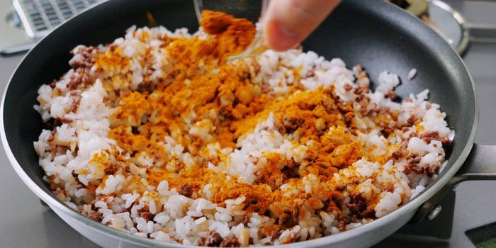 Curry powder sprinkled on top of fried rice.