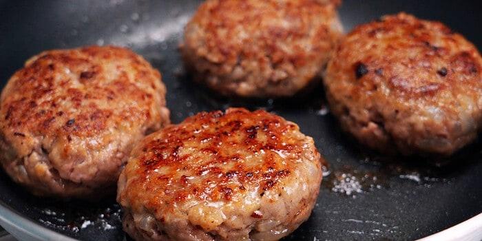 Browned Japanese hamburger steaks in a frying pan.