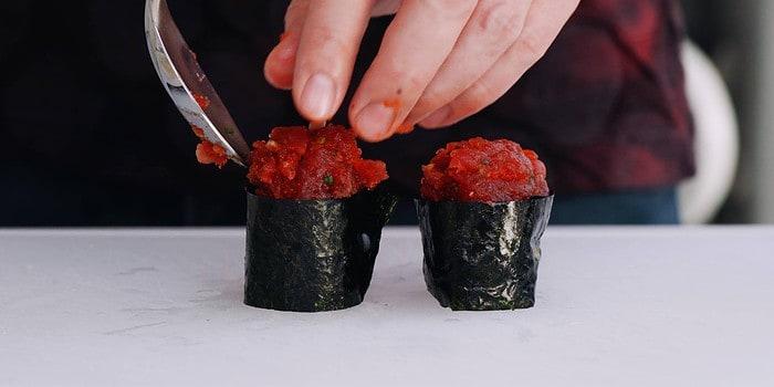 Adding spicy tuna to gunkan roll.