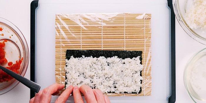 Sushi rice on nori for making spicy tuna hosomaki.