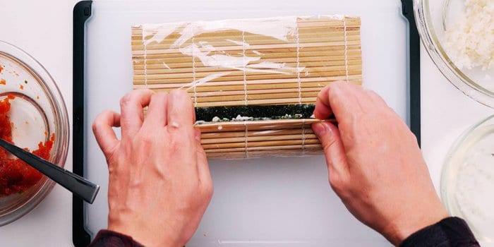 Rolling hosomaki with a sushi mat.