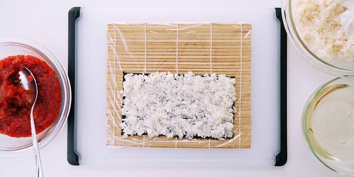 Rice on nori for uramaki style spicy tuna roll.
