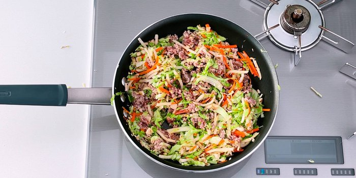 Vegetables and meat stir-frying for making Japanese spring rolls.