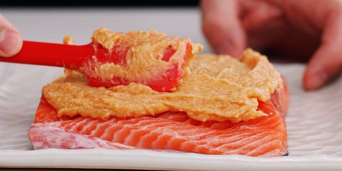Spreading miso butter on a piece of salmon.
