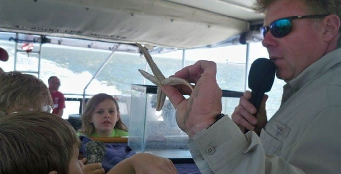 Speaker holding up a starfish for the kids to admire. Party boat fishing Charleston, SC
