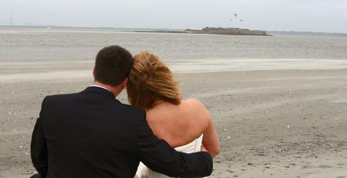 Bride and Groom sitting on the beach looking out on the water. Wedding dinner cruise Charleston SC