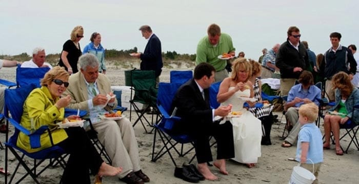 Wedding party enjoying their dinner on the beach. Wedding dinner cruise Charleston SC