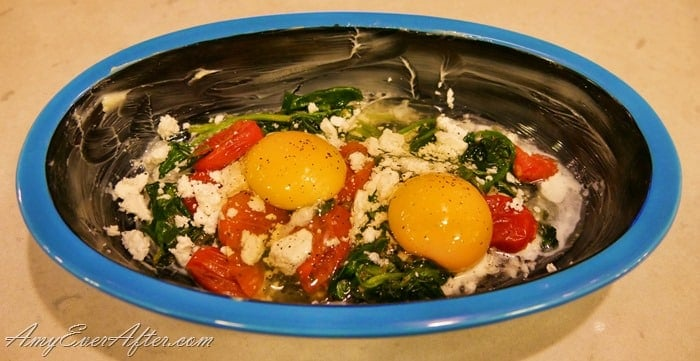 blue dish with tomatoes, spinach, feta cheese, and 2 eggs