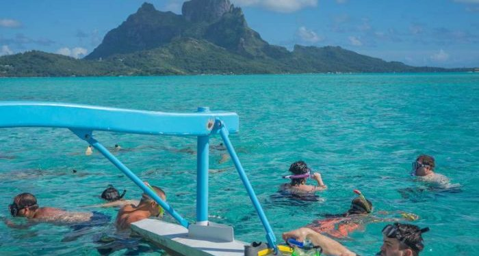 snorkeling in crystal clear blue water off of Bora Bora