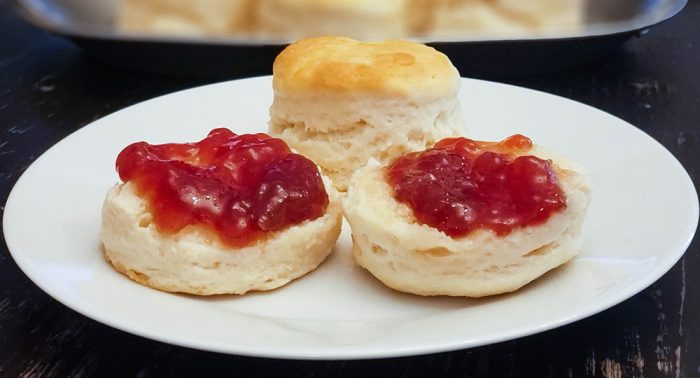 Homemade buttermilk biscuits on a plate, with jam