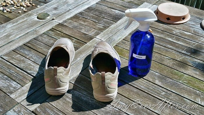 smelly shoes and blue glass spray bottle of vodka on a wooden table
