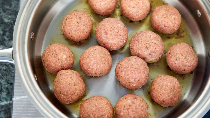 The best meat balls are pan fried, this forms a brown crust around the meatball that adds flavor to the marinara sauce.