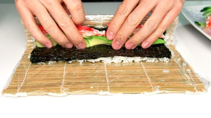 Roll one edge of the rice and nori over the fillings.