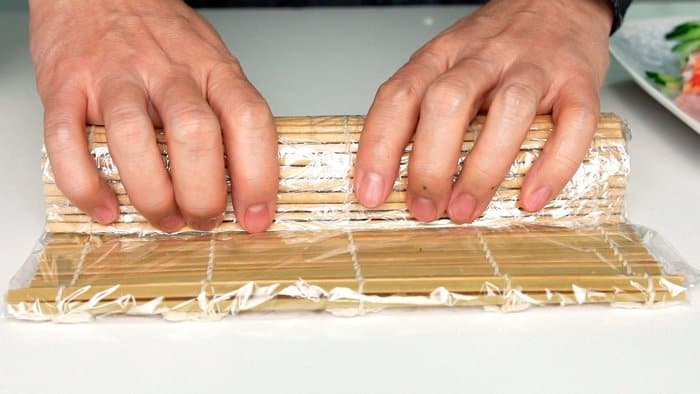 The bamboo sushi matt helps shape the sushi roll.