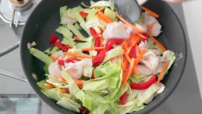 Stir-fried cabbage, carrots, red bell peppers and chicken for making Chicken Chow Mein.
