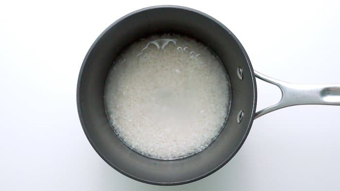 Sushi rice soaking in water before cooking.