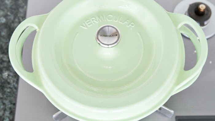Green dutch oven covered with a lid on a a grey stove.