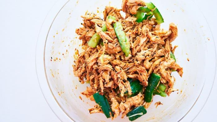 Chicken and crushed cucumbers tossed with bang bang chicken sauce in a glass bowl.