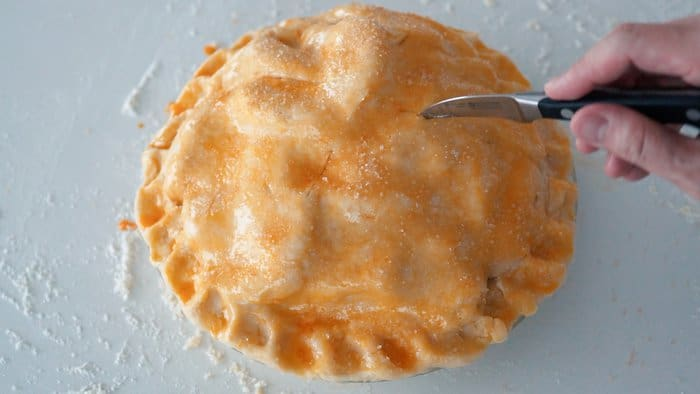 Cutting holes into the top of an apple pie to allow steam to vent.