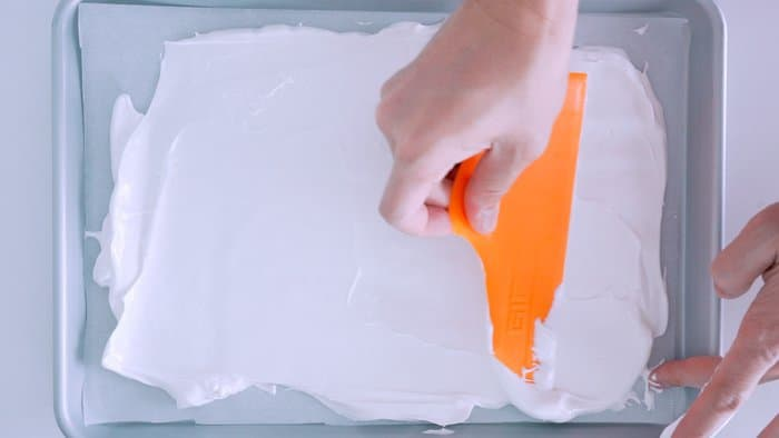 Spreading meringue into a thin layer on a baking sheet.