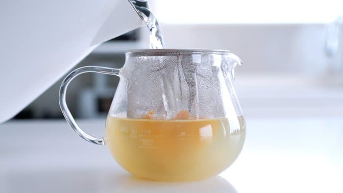 Adding boiling water to a teapot with ginger and lemon zest.